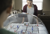 Smiling boy playing ice hockey game at home