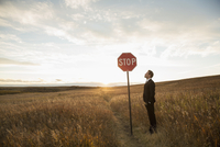 Businessman looking at stop sign in field