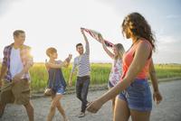 Friends holding up an American flag outdoors 11096036219| 写真素材・ストックフォト・画像・イラスト素材|アマナイメージズ