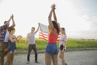 Friends holding up an American flag outdoors 11096036283| 写真素材・ストックフォト・画像・イラスト素材|アマナイメージズ