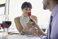 Thoughtful man giving woman rose in restaurant