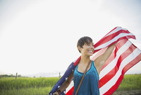 Young woman holding American flag outdoors