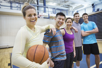 Portrait of men and women with basketball in gym