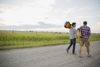 Young men with guitar and backpack walking on country road