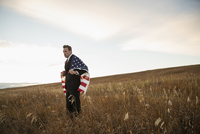 Businessman holding American Flag on field
