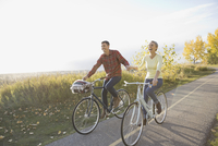 Happy couple cycling on country road