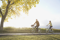 Couple cycling on country road 11096037340| 写真素材・ストックフォト・画像・イラスト素材|アマナイメージズ