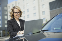Businesswoman using laptop on car hood outdoors
