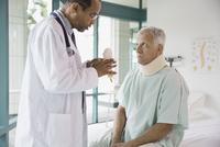 Doctor explaining model to patient suffering from neck pain