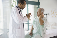 Senior patient discussing neck pain with doctor