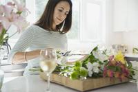 Woman arranging flowers in kitchen 11096037799| 写真素材・ストックフォト・画像・イラスト素材|アマナイメージズ
