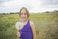 Portrait of girl holding a Tragopogon plant in field 11096037858| 写真素材・ストックフォト・画像・イラスト素材|アマナイメージズ