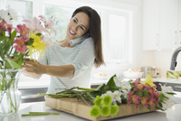Woman talking on phone in kitchen while arranging flowers