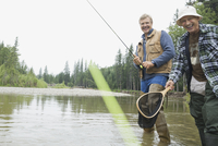 Portrait of happy senior man fishing with son