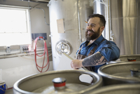 Brewery worker with clipboard leaning on kegs