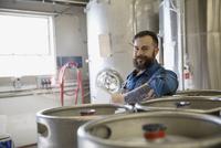 Portrait of brewery worker leaning on kegs