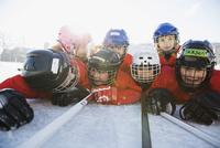 Cheerful hockey team lying on ice rink