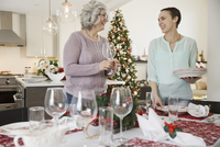 Mother and daughter setting dining table during Christmas