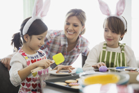 Mother with children decorating Easter cookies