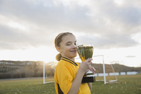 Portrait of player holding trophy on soccer field