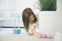 Girl collecting Easter eggs at home