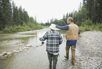 Rear view of men walking with fishing gear