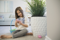 Girl collecting Easter eggs at home 11096038956| 写真素材・ストックフォト・画像・イラスト素材|アマナイメージズ