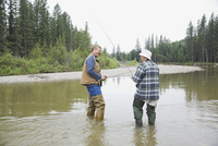 Father and son with fishing rods standing in river