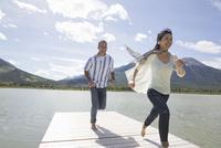 Mature couple running on dock 11096039072| 写真素材・ストックフォト・画像・イラスト素材|アマナイメージズ