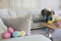 Colorful Easter eggs behind cushion on sofa 11096039087| 写真素材・ストックフォト・画像・イラスト素材|アマナイメージズ