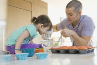 Father and daughter baking cupcakes in kitchen