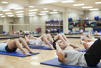Group of people doing sit-ups in fitness class