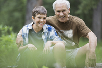Portrait of happy grandfather and grandson sitting outdoors