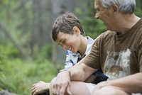 Happy boy sitting with grandfather in forest
