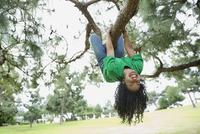 Happy female volunteer hanging upside down from tree branch