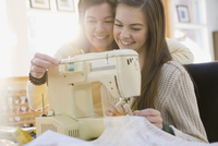 Mother teaching daughter how to use sewing machine