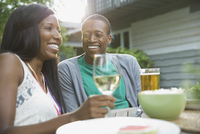 Cheerful couple enjoying a drink outdoors