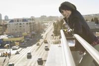 Portrait of smiling woman leaning against patio railing 11096040335  写真素材・ストックフォト・画像・イラスト素材 アマナイメージズ