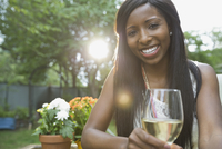 Portrait of smiling woman holding wineglass in yard