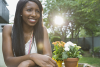 Thoughtful woman smiling while relaxing outdoors