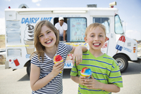 Portrait of cheerful little friends holding ice creams against van