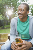 Smiling man relaxing with a drink in backyard