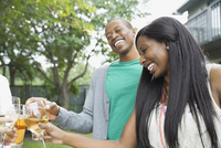 Cheerful couple toasting drinks with friends outdoors