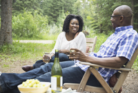 Happy couple relaxing with wine outdoors
