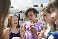 Happy children enjoying ice creams together outdoors