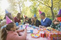 Multi-generation family celebrating girls birthday in park