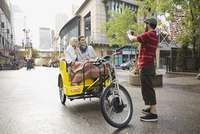 Driver photographing couple in rickshaw