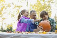 Smiling grandfather and grandchildren preparing jack o lantern in park 11096041267| 写真素材・ストックフォト・画像・イラスト素材|アマナイメージズ