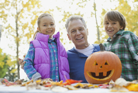 Portrait of happy children and grandfather with jack o lantern in park