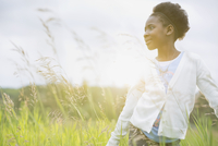 Girl standing in field looking away